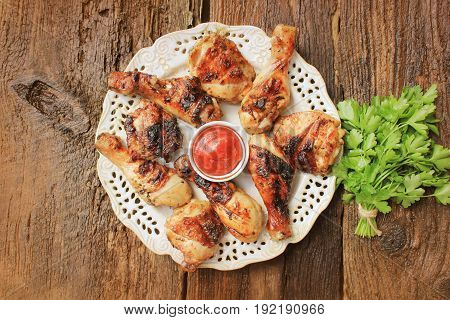 Grilled chicken legs on wooden table served on white plate with coriander . Top view .