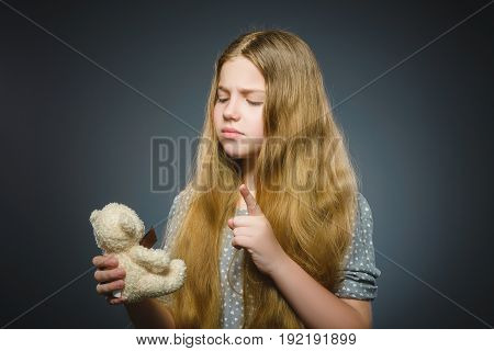 portrait of worried girl playing with teddy bear isolated on gray.