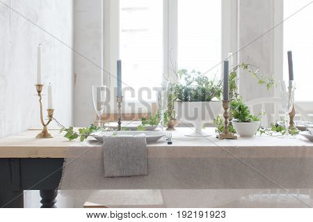 Horizontal indoors shot of served table at white wall in dining room. Decorated with flowers and ivy