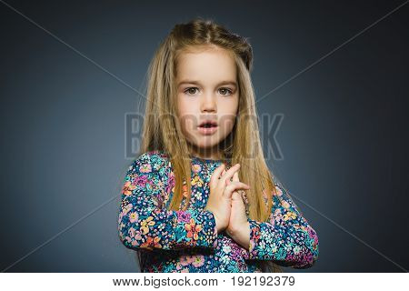 Closeup Portrait of little girl going surprise on gray background.