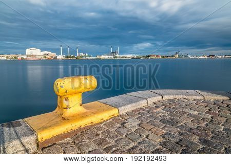 Scenic view of the skyline of Copenhagen at sunset from dock with yellow bollard on foreground