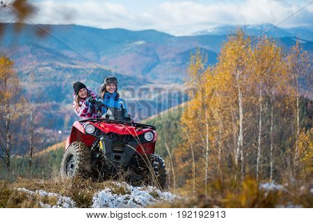 Happy Females Atv Driver In Winter Clothing On Snowy Hills On The Background Of Mighty Mountains And