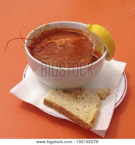 Spicy maltese shrimp soup. Shrimp soup with seafood. Seafood. Shrimp soup served with bread and lemon in orange background. Maltese food.