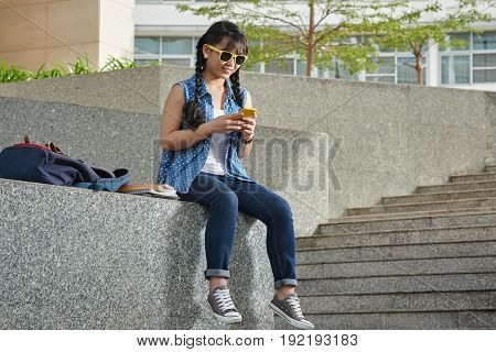 Smiling young student sitting outdoors and texting with her friend on smartphone while having interval between lectures, full length portrait