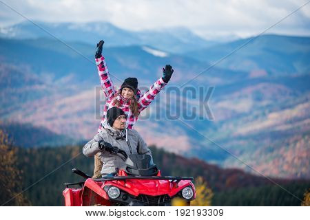 Close-up Of Man Driving Atv Quad Bike, Girl Sitting Behind Him And Raised Her Hands Up On Blurred Ba