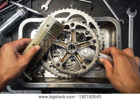 Hand of a mechanic cleaning a bicycle cassette and crankset