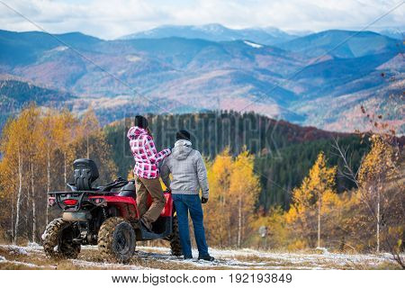 Rear View Of Girl Standing On A Red Quad Bike And Keeps The Shoulder Standing Next Guy Enjoying The