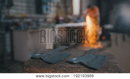 Blacksmith workshop - grinding iron knifes with sparkles, blurred