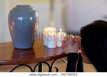 cremation, people and mourning concept - sad woman with cinerary urn and candles praying at funeral in church