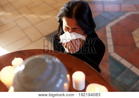 cremation, people and mourning concept - woman with wipe and cinerary urn crying at funeral in church