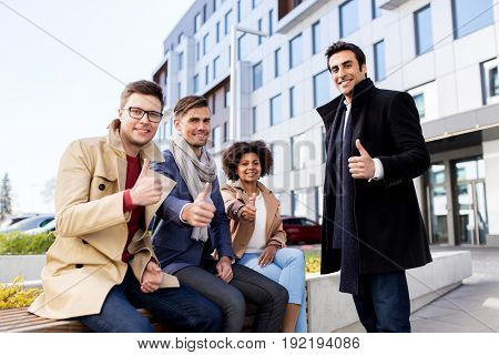 business, gesture and corporate concept - international group of people showing thumbs up outdoors