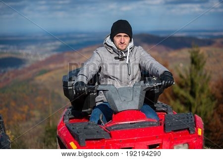 Close-up Of Guy In Winter Clothing On Red Quad Bike Looking At The Camera On The Blurred Background
