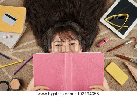 Head and shoulders portrait of happy Vietnamese woman covering her face with notebook while lying on messy floor, directly above view