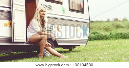 Young and beautiful hippy girl sitting on trailer at summer. Holiday, journey, vacation concept.