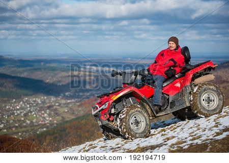 Man In Winter Clothes Resting On A Red Atv Bike On A Snowy Mountain Top, Looking To The Camera On A
