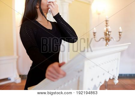 people and mourning concept - woman with wipe at funeral in church