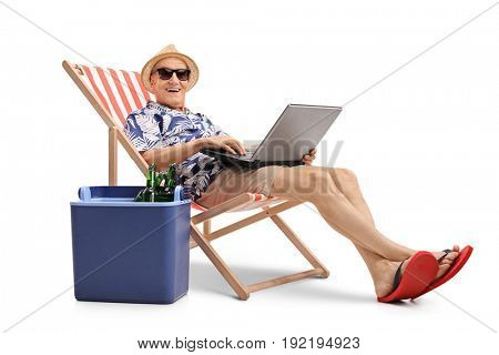 Elderly tourist with a laptop sitting in a deck chair next to a cooling box and looking at the camera isolated on white background