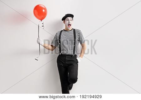 Mime holding a balloon and leaning against a wall
