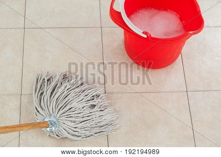 Red bucket with foamy water and mopping the tile floor