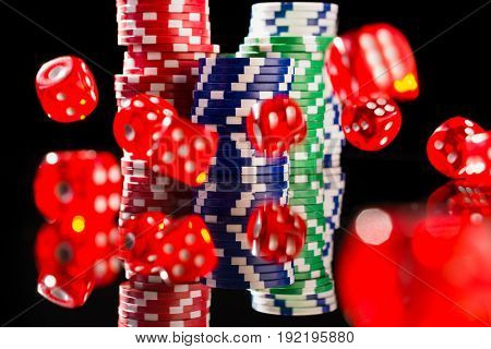 Dice and casino chips on black background