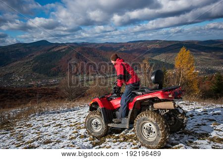 Sports Atv Quad Bike With Driver At The Snow-covered Hill Against The Blue Cloudy Sky, Mountains And