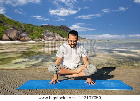 fitness, sport, yoga, people and healthy lifestyle concept - man making scale pose lotus variation on mat over exotic tropical beach background