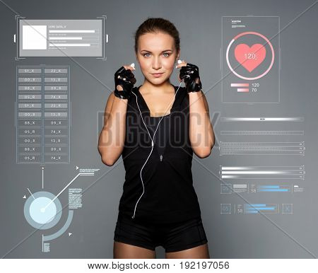 sport, fitness and technology concept - young woman with earphones listening to music in gym