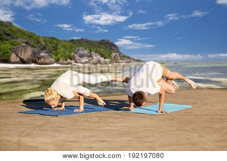 fitness, sport, yoga and people concept - couple making side crane pose on mat over exotic tropical beach background