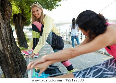 Female runners stretching outdoors, smiling happy.