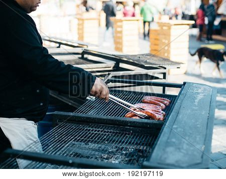 Man cooking sausages on barbecue on street market