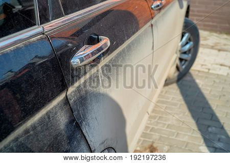 Close-up image of dirty car side required to be washed