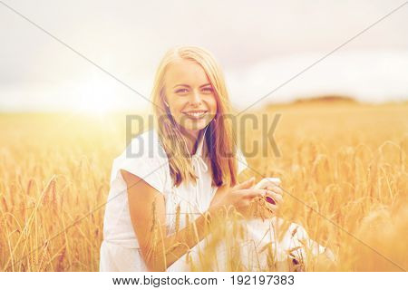 summer holidays, vacation, technology and people concept - smiling young woman in white dress with smartphone and earphones listening to music on cereal field