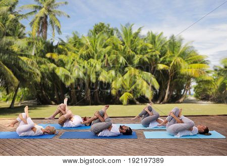 fitness, sport, yoga and healthy lifestyle concept - group of people making half ankle to knee supine pose over natural exotic background with palm trees