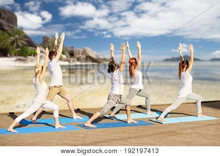 fitness, sport, yoga and healthy lifestyle concept - group of people making high lunge or crescent pose over exotic tropical beach and sea shore background