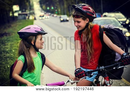 Bicyclist child ride on bicycle path in city. Girls wearing helmet with rucksack . Cyclists stopped and talked to each other. Kid move on yellow bike lane. Cars drive road on background tone image.
