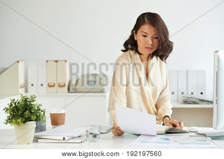 Concentrated Asian businesswoman reading carefully document at office desk