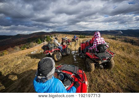 Group Of People Riding A Off-road Vehicles On A Mountain Road Under Beautiful Sky With Clouds In Aut