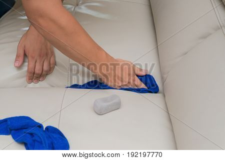 cleaning leather sofa with sponge and towels at home
