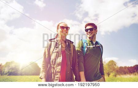travel, hiking, backpacking, tourism and people concept - happy couple with backpacks holding hands and walking outdoors