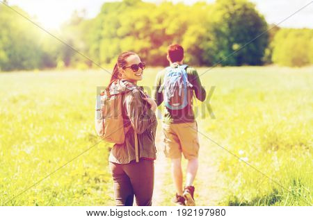 travel, hiking, backpacking, tourism and people concept - happy couple with backpacks walking along country road outdoors
