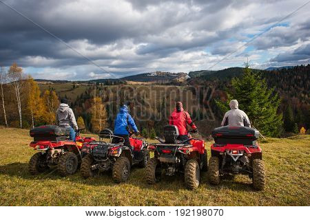 Rear View Of Four Men At Quad Bikes Prepared To Go Down The Hill. Beautiful Landscape Of Rolling Cou