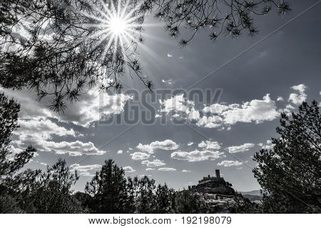Wide angle backlit of castle on top of hill with sun ray lights