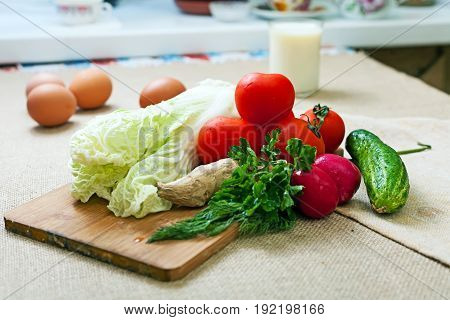 Fresh vegetables on a cutting board. Tomatoes and parsley with salad. Close-up.
