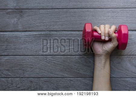 woman hand holding red dumbbell on wood tale background