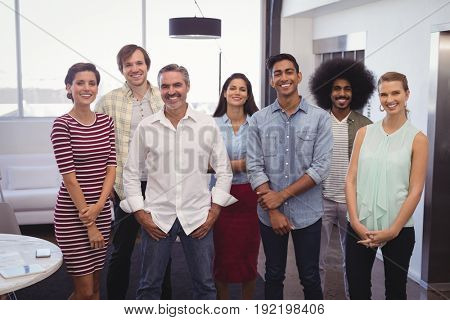 Portrait of smiling business team standing in creative office