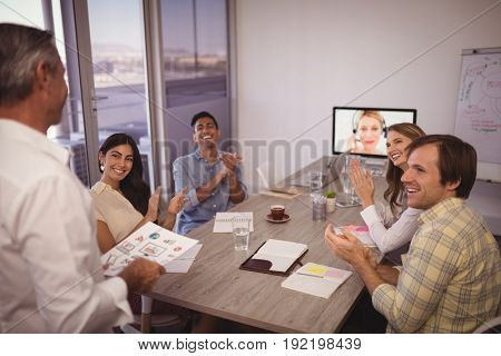 Colleagues applauding for mature businessman giving presentation in conference room