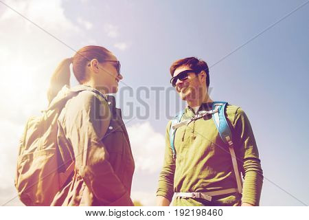 travel, hiking, backpacking, tourism and people concept - happy couple with backpacks talking outdoors