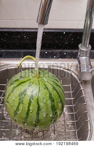 cooling a watermelon on sink with water