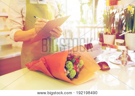people, sale, retail, business and floristry concept - close up of florist man with clipboard and bunch writing and making notes at flower shop counter