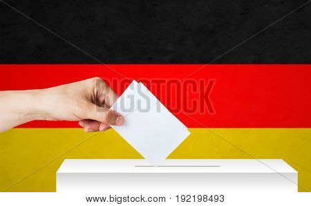 voting, civil rights and people concept - male hand putting his vote into ballot box on election over german flag background
